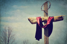 crown of thorns and a red shroud on a cross