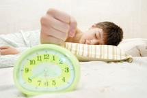 a sleepy teen boy hitting an alarm clock