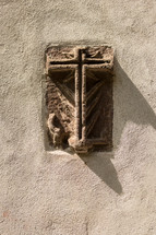 stone cross engraved in the side of a wall