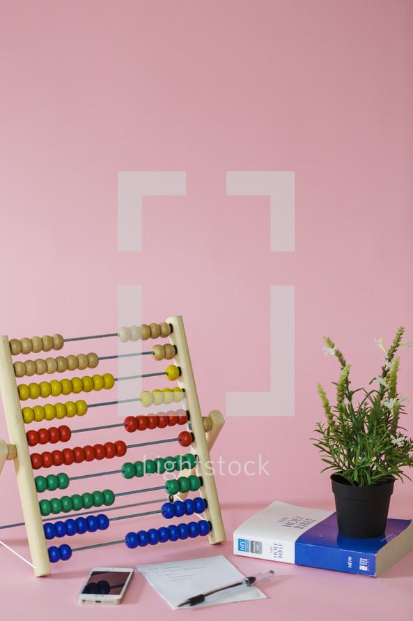abacus, cellphone, paper, pen, Bible, house plant