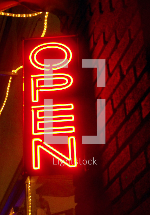An Orange Neon Open Sign lights up the downtown with a warm orange glow announcing that the store is open for business and taking customers. An orange neon sign lights up the brick wall with a warm orange glow so people can see the sign for blocks away.