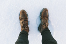 Feet in boots standing in snow.