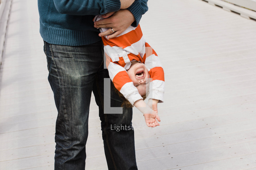 A laughing little boy being held upside down.