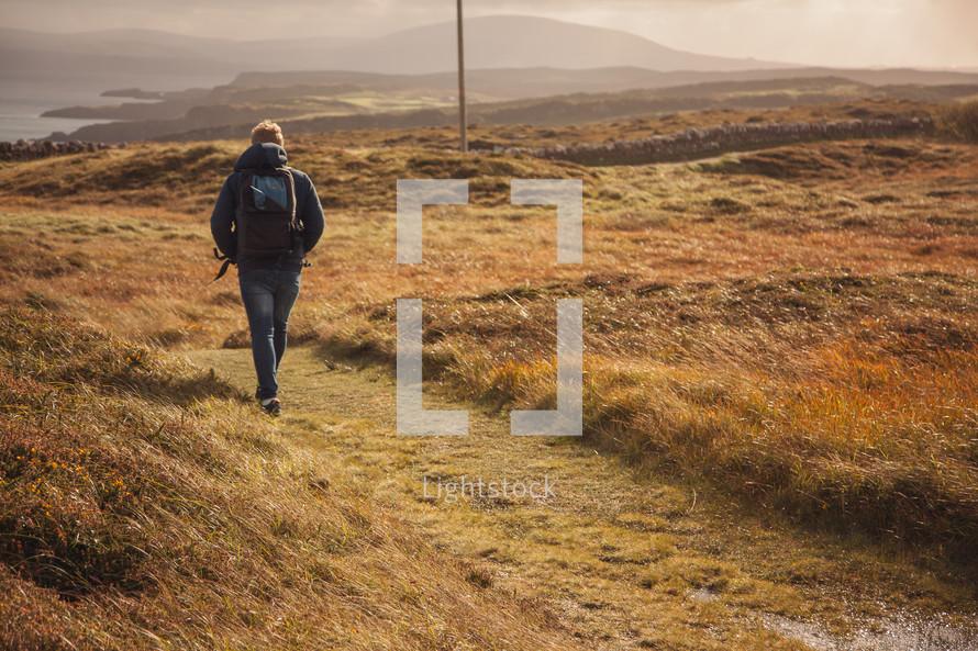 a man hiking towards a shoreline