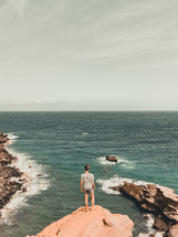 woman standing at the edge of a cliff overlooking the ocean