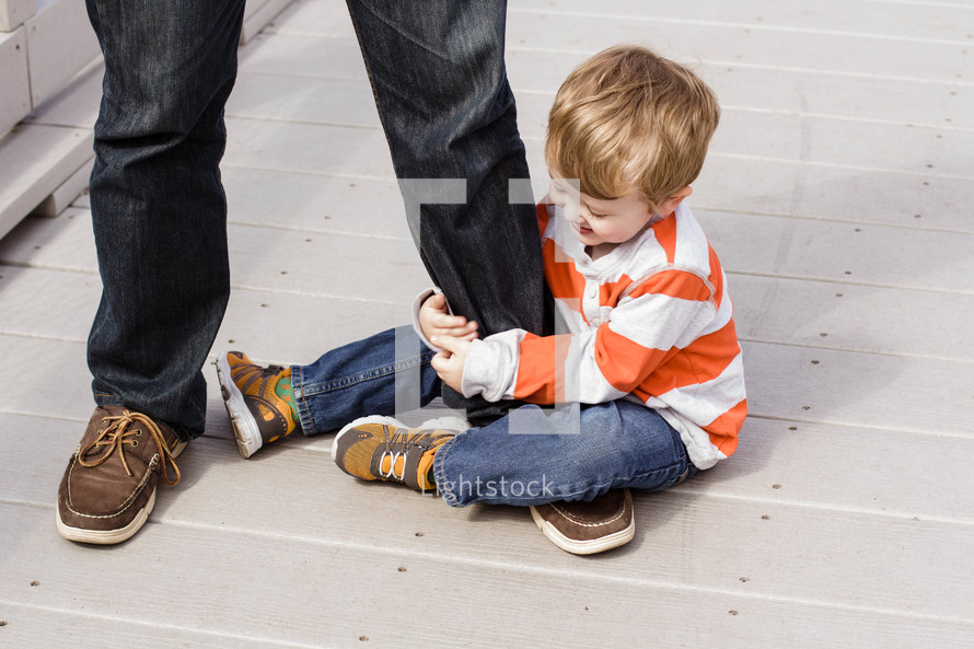 A little boy sits on the ground holding his father's leg.