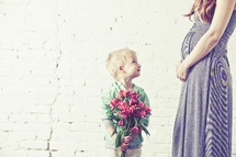 Boy giving bouquet of flowers to his mother.