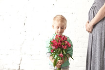 little boy holding a bouquet of flowers for his mother
