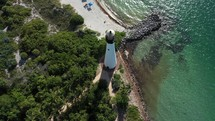 Cinematic Aerial  pull-back view of the lighthouse, tourist and the beach