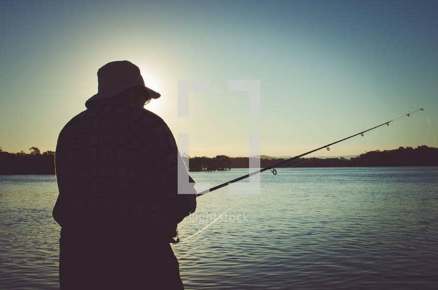 a man fishing at dusk
