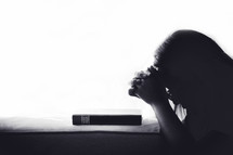 Silhouette woman praying on holy bible in the morning