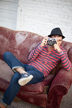 man sitting on an old couch outdoors taking a picture with a camera