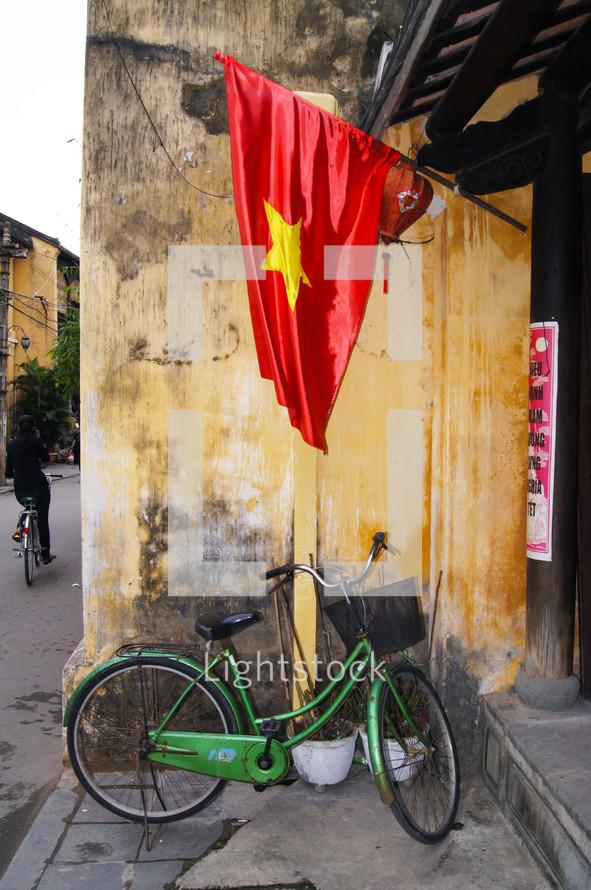 A bike sitting under a Vietnamese flag