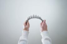 woman holding up tiara