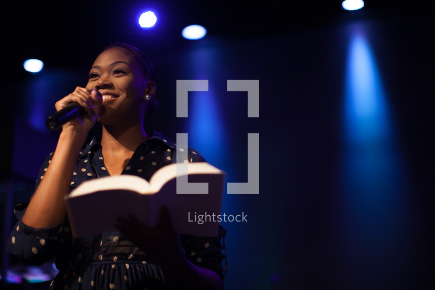A woman holding a microphone leading a worship service