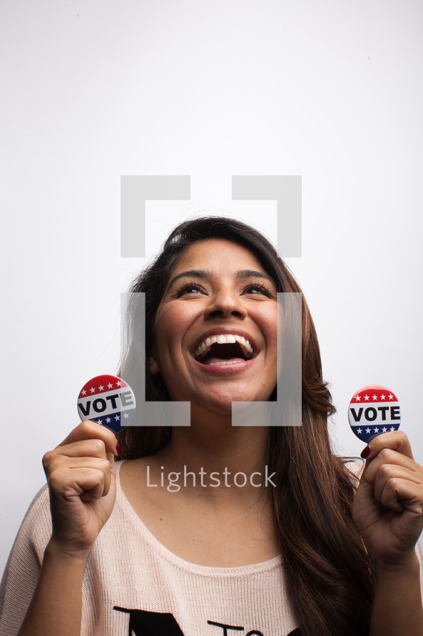 young woman holding vote buttons