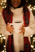 a woman holding a mug of hot cocoa standing in front of a Christmas tree