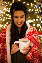 a woman wrapped in a blanket holding a mug of hot cocoa