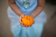 a child in a princess costume holding a pumpkin