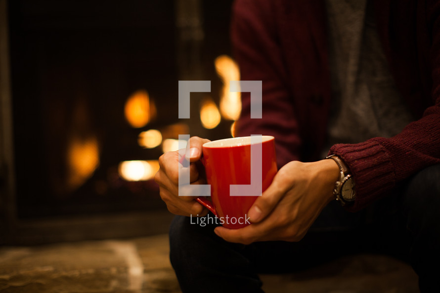 sitting in front of a fireplace holding a mug
