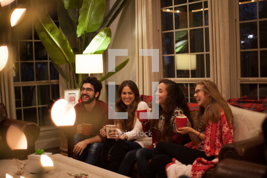 people sitting on a couch drinking hot cocoa and talking at a Christmas party