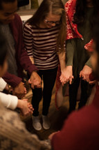 holding hands in prayer at a Christmas party