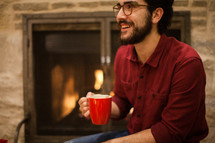 a man with a mug of hot cocoa sitting in front of a fireplace