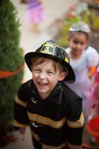 children trick or treating on a neighborhood sidewalk on Halloween