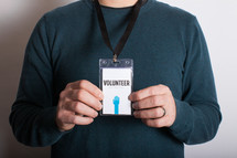 A man holding out a volunteer badge which he is wearing around his neck.