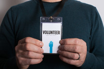 A man holding out a volunteer badge which is around his neck.