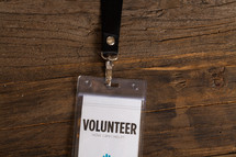 A volunteer badge clipped to a lanyard.
