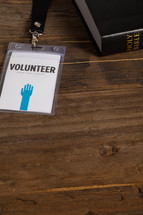 A volunteer badge on a table next to a Bible.