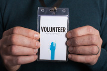 A man holding a volunteer badge with both hands.