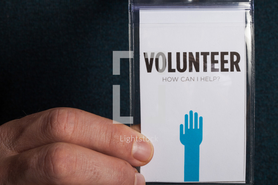 A hand holding a volunteer badge.