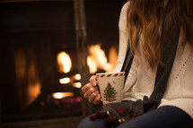 a woman sitting in front of a fireplace holding a mug of hot cocoa