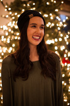 a smiling woman standing in front of a Christmas tree