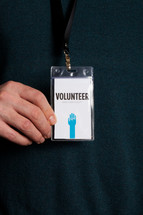 A man wearing a volunteer badge around his neck.