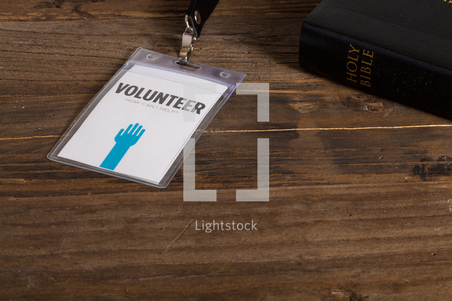 A volunteer badge holder on a table next to a Bible.