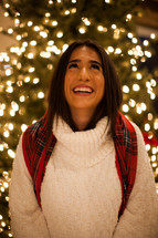 a happy woman standing in front of a Christmas tree looking up