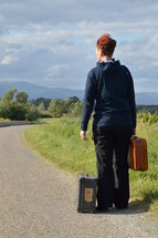 woman on the road with old suitcases