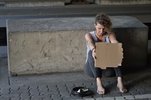 a homeless woman holding a blank sign under a bridge