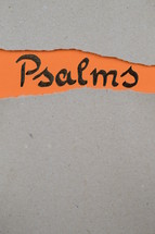torn open kraft paper over orange paper with the name of the book of Psalms