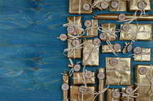 Border of advent calendar with twenty four golden presents on teal wood with negative space to the left