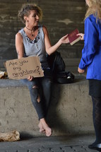 a woman giving a Bible to a woman under a bridge