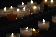 many lit candles in a dark church.  candle, lit, flame, fire, burning, candles, flames, kindled, light, lighted, blaze, blazing, burning, burn, many, much, lot, dark, lighten, brighten, bright, illuminate, illumine, shine, shining, see, seeing, show, showing, symbol, symbolic, symbolize, symbolizing, believe, believers, wax, church, pray, prayer, votive, darkness, burnt, donation, donate, ceremony, offering, offer, yellow, white, orange, row, line, lines, commemorate, remember, recall, remembrance, memory, memento, think of, sign, creed, unlit, rows