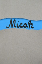 torn open kraft paper over blue paper with the name of the prophetic book Micah