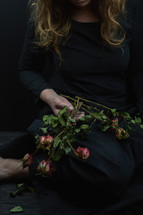 a woman holding a bouquet of dead roses