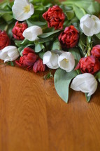 Red and white tulips on a wooden table.