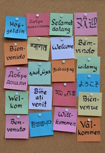 welcome in various languages on sticky notes on a cork board