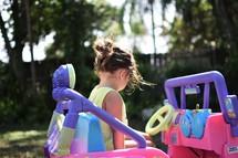 a little girl in a power wheels jeep